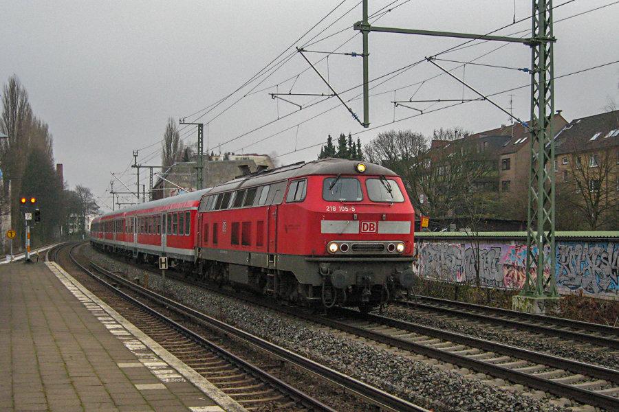 218 105 mit einem Regionalzug bei der Vorbeifahrt am S-Bahn Haltepunkt Landwehr.