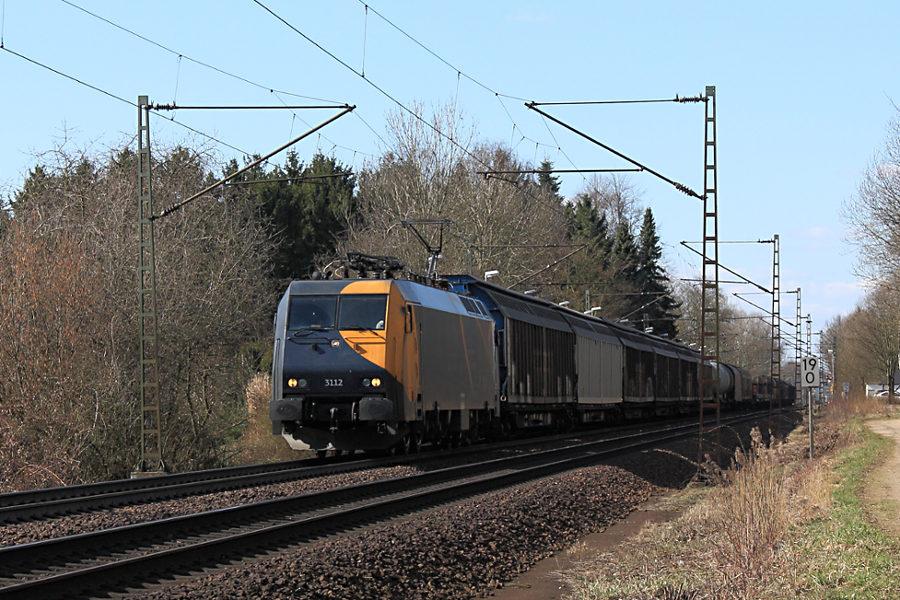 EG3112 mit Güterzug durchfährt den Haltepunkt Prisdorf.