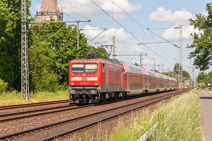 112 152 mit RE 21023 nach der Durchfahrt durch den Bahnhof Brokstedt.