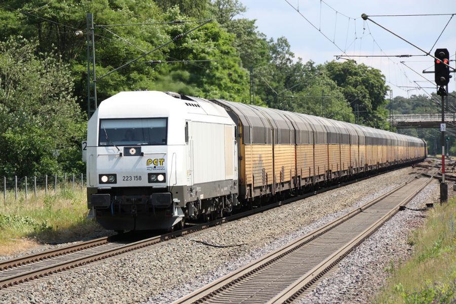 223 158 durchfährt mit einem Neuwagenzug den Bahnhof Lauenbrück.
