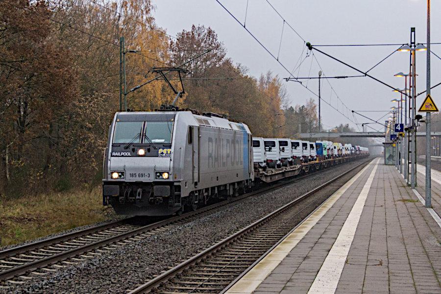 185 691 durchfährt mit einem PCT-Autotransportzug den Bahnhof Lauenbrück.