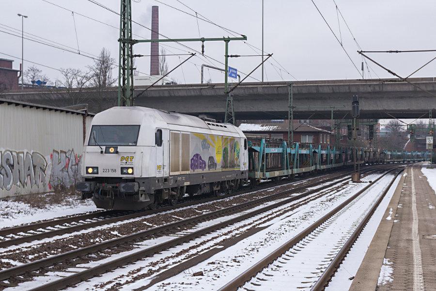 223 158 durchfährt mit einem Autotransportzug den Bahnhof Hamburg-Harburg.