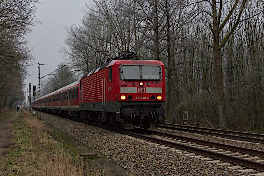 143 930 mit einem RE vor der Durchfahrt durch den Haltepunkt Prisdorf.