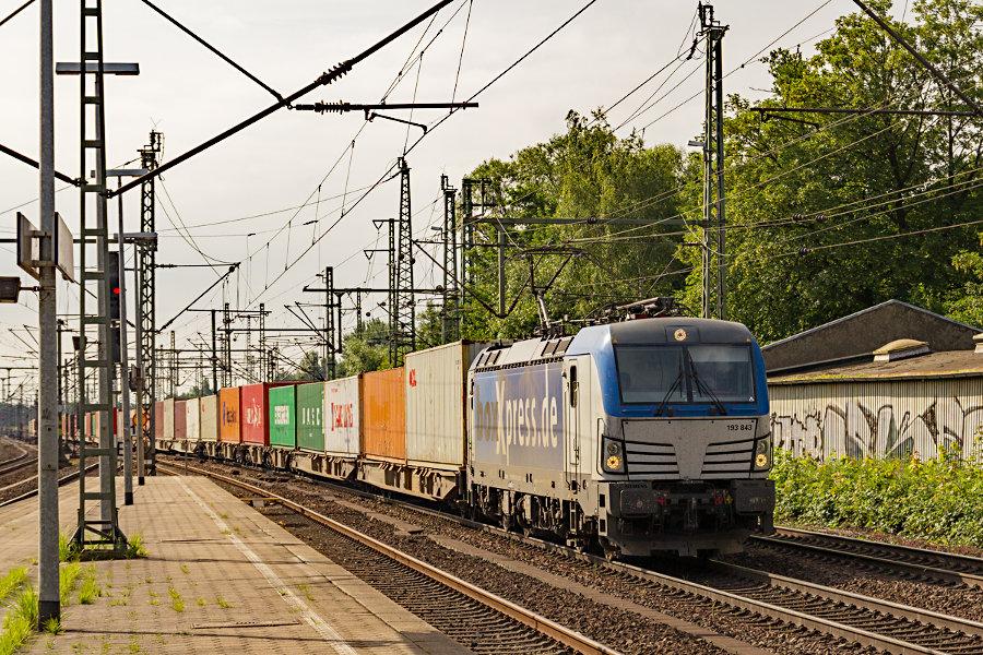 193 843 durchfährt mit einem Containerzug den Bahnhof Hamburg-Harburg.