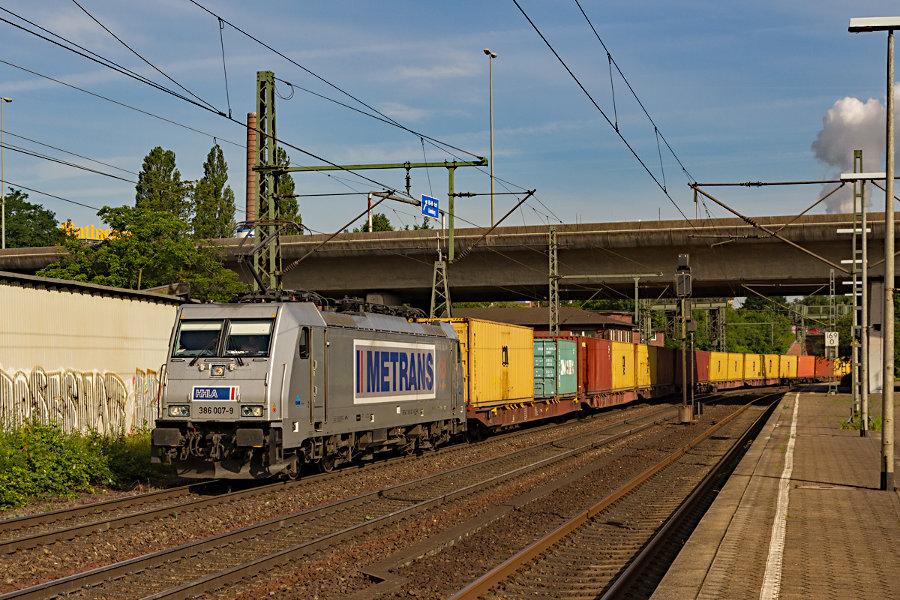 386 007 durchfährt mit einem Containerzug den Bahnhof Hamburg-Harburg.
