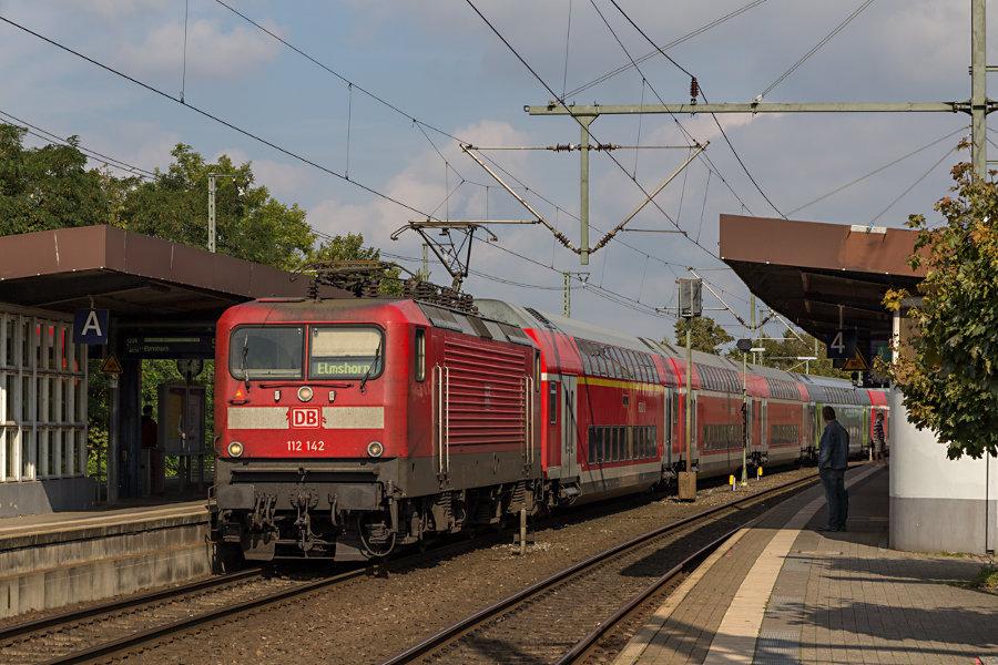 112 142 mit RE 21069 (RE7) beim Halt im Bahnhof Neumünster.