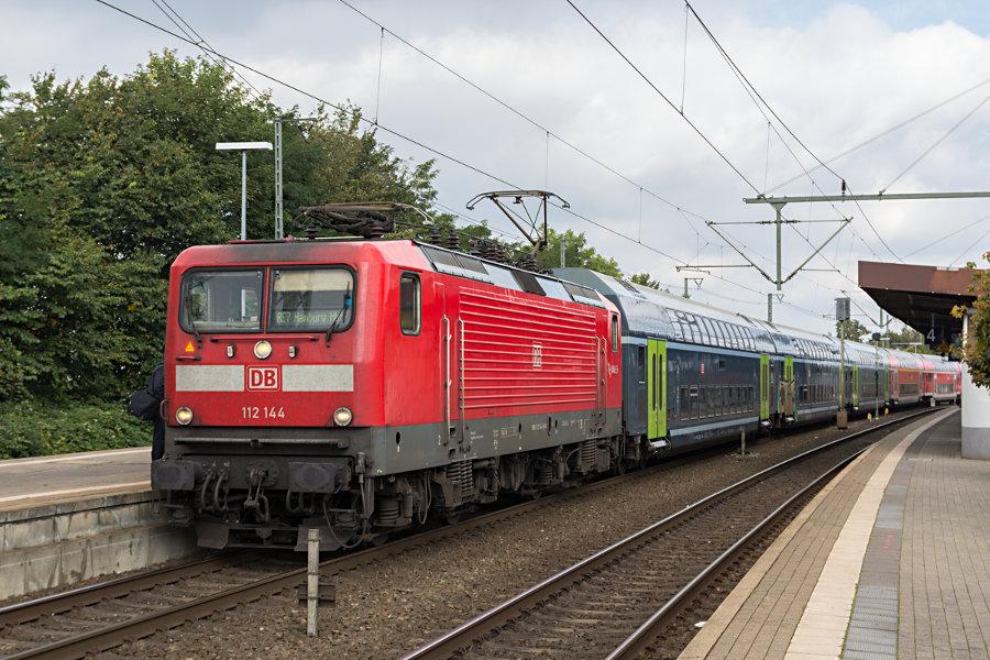 112 144 mit RE 21017 (RE7) beim Halt im Bahnhof Neumünster.