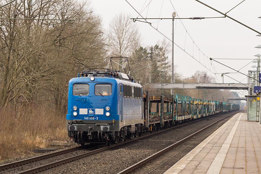 140 050 (140 833) durchfährt mit einem Autotransportzug den Bahnhof Lauenbrück